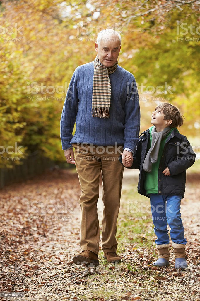 Grandfather And Grandson Walking Along Autumn Path royalty-free stock photo