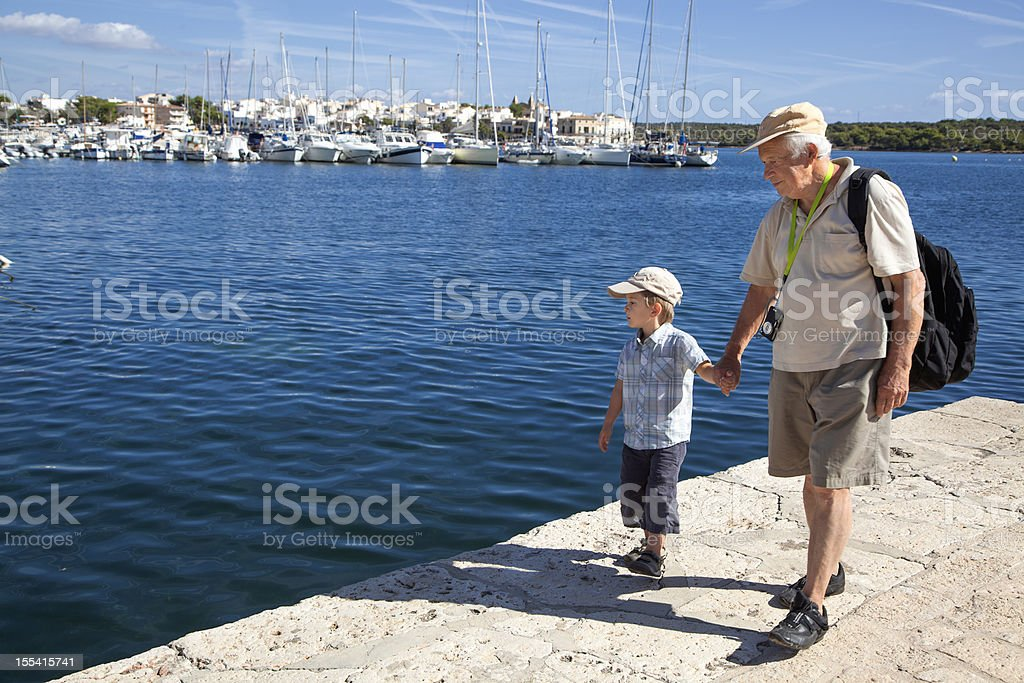 Grandfather And Grandson Walking On Waterfront in Harbour royalty-free stock photo