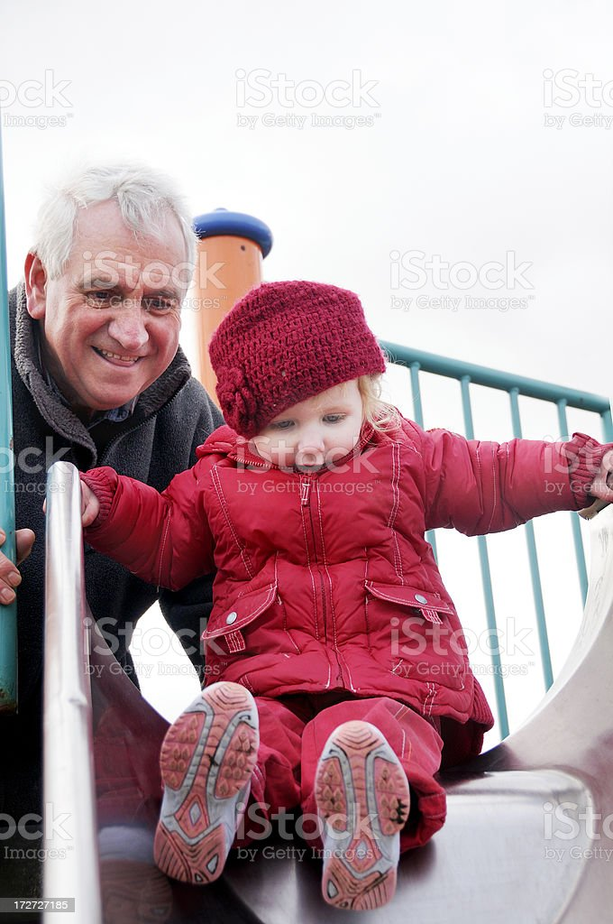 grandfather and granduaghter on slide stock photo