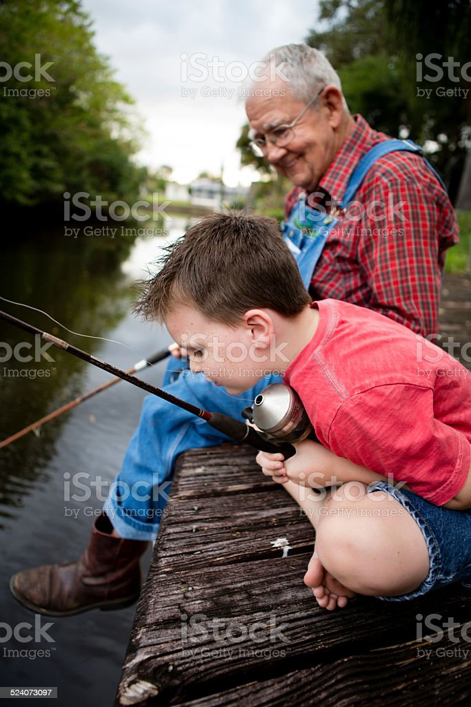 Grandfather and Great Grandson Fishing on Wood Dock stock photo