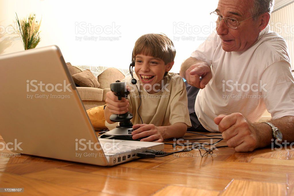 A grandfather and his grandson enjoying video games royalty-free stock photo