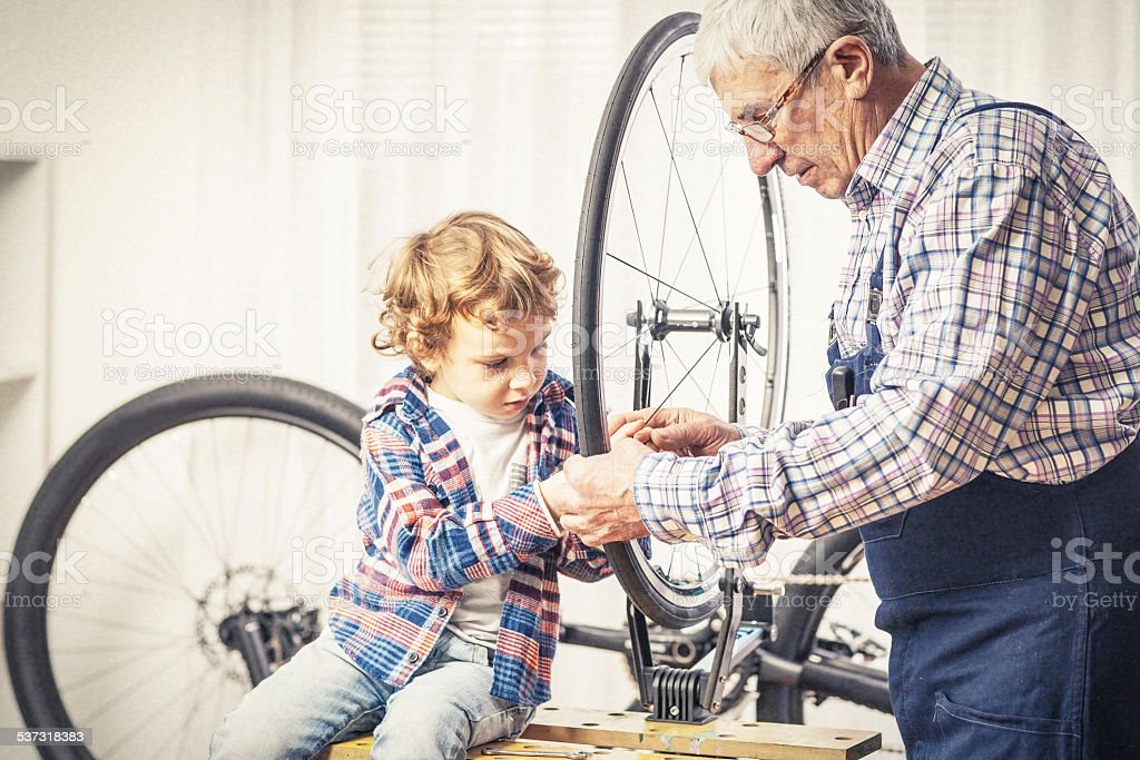 Grandfather and his grandson repairing a bicycle stock photo