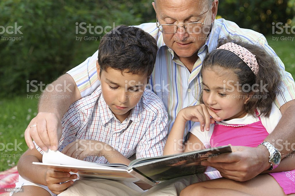 Grandfather and kids reading book royalty-free stock photo