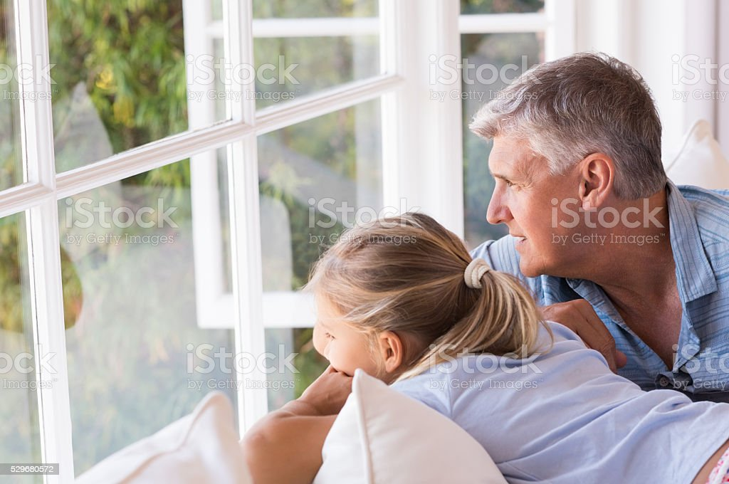 Grandfather and little girl thinking stock photo