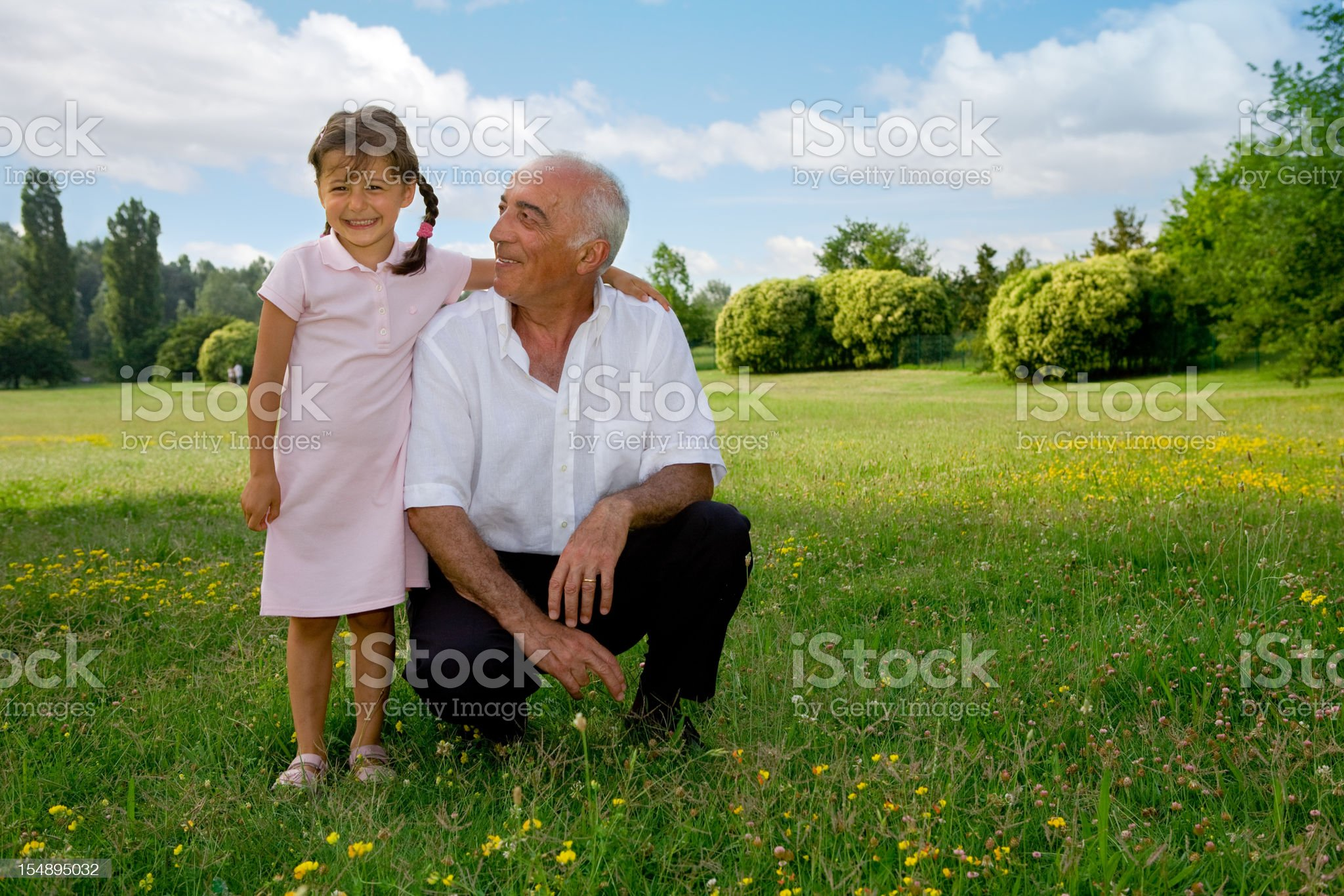 Grandfather and niece over green field royalty-free stock photo