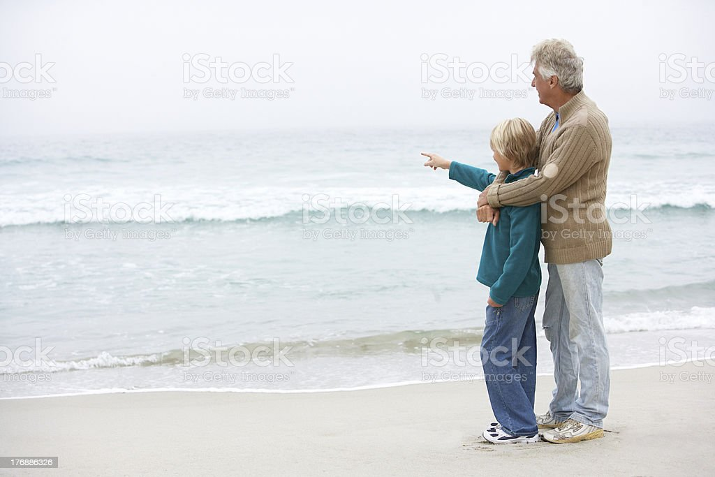 Grandfather And Son Standing On Winter Beach Together royalty-free stock photo