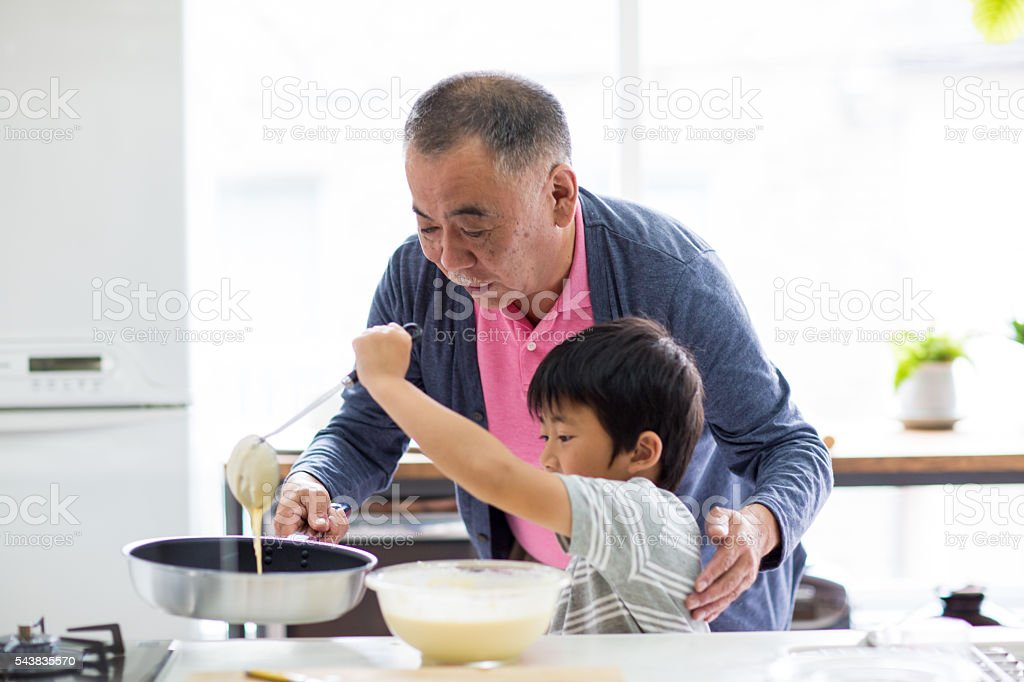 Grandfather and young grandson making pancakes together stock photo
