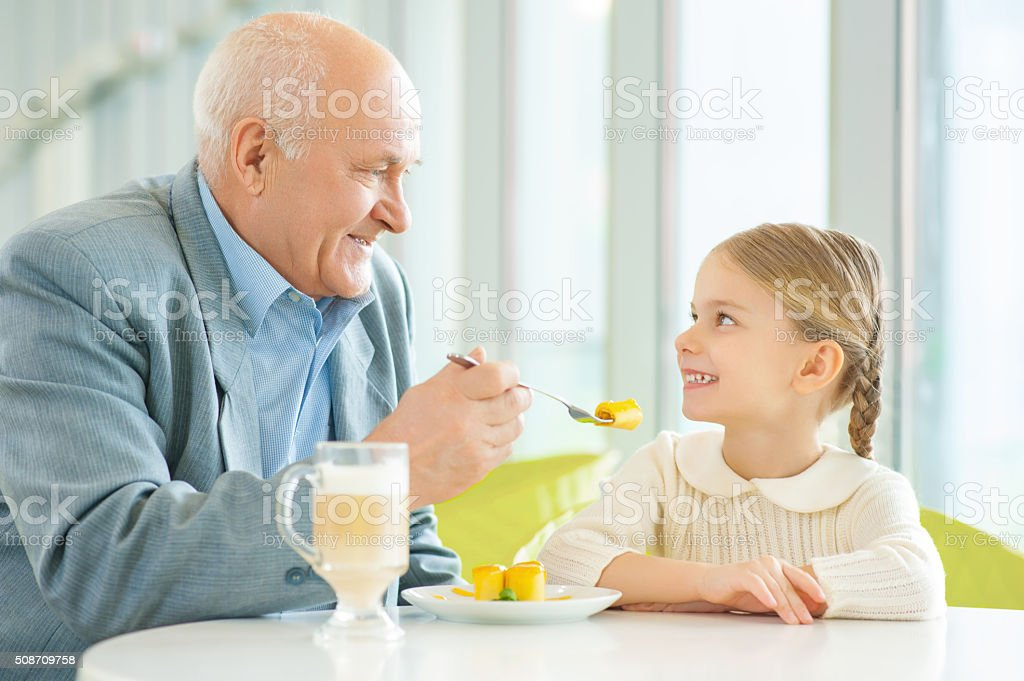 Grandfather asking granddaughter to try a pie stock photo