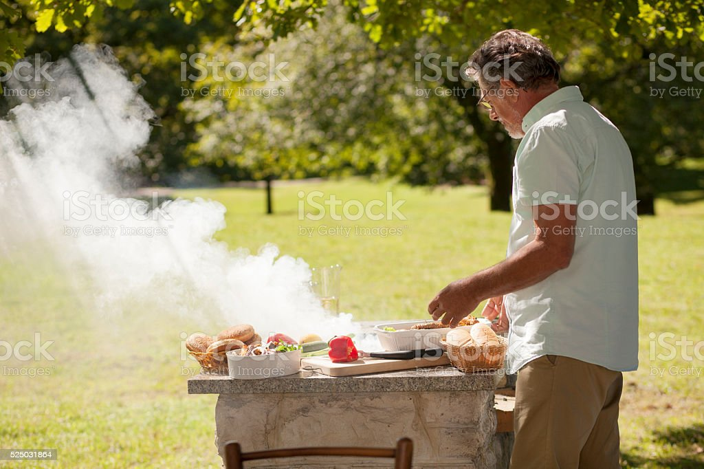 Grandfather at barbecue stock photo