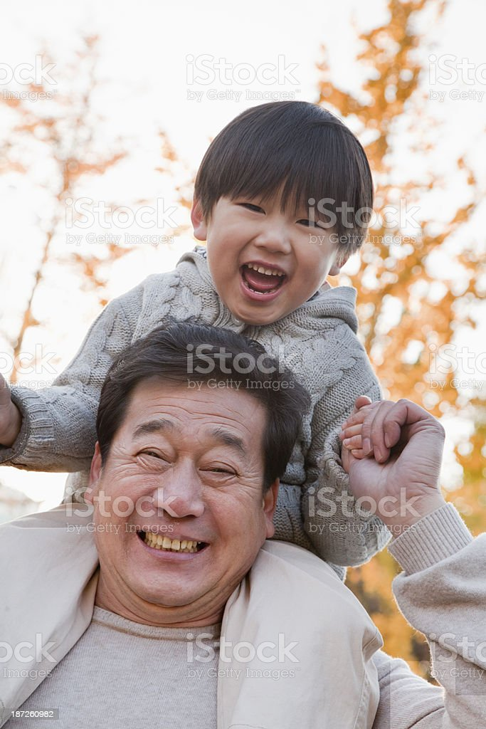 Grandfather Carrying Grandson on His Shoulders royalty-free stock photo