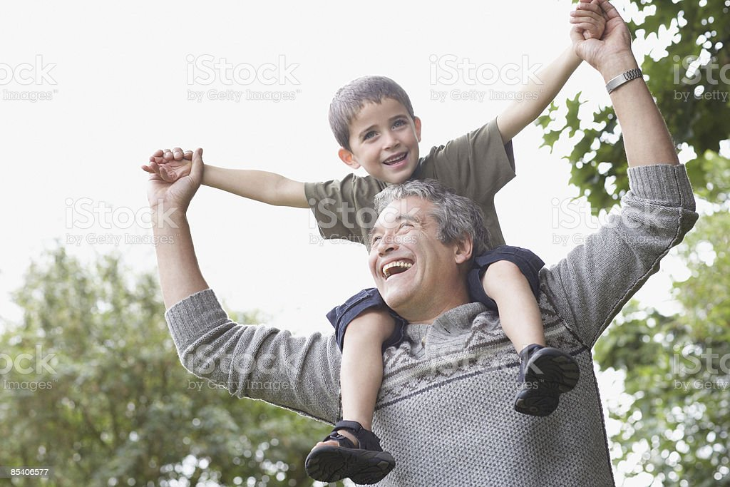 Grandfather carrying grandson on shoulders royalty-free stock photo
