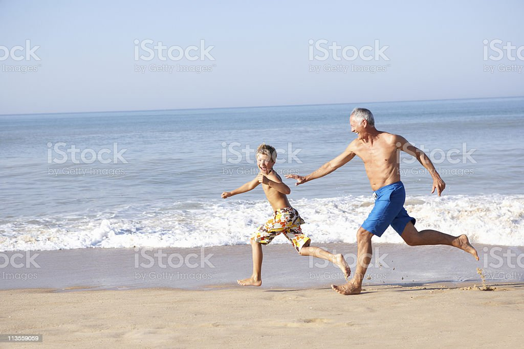 Grandfather chasing grandson on beach royalty-free stock photo