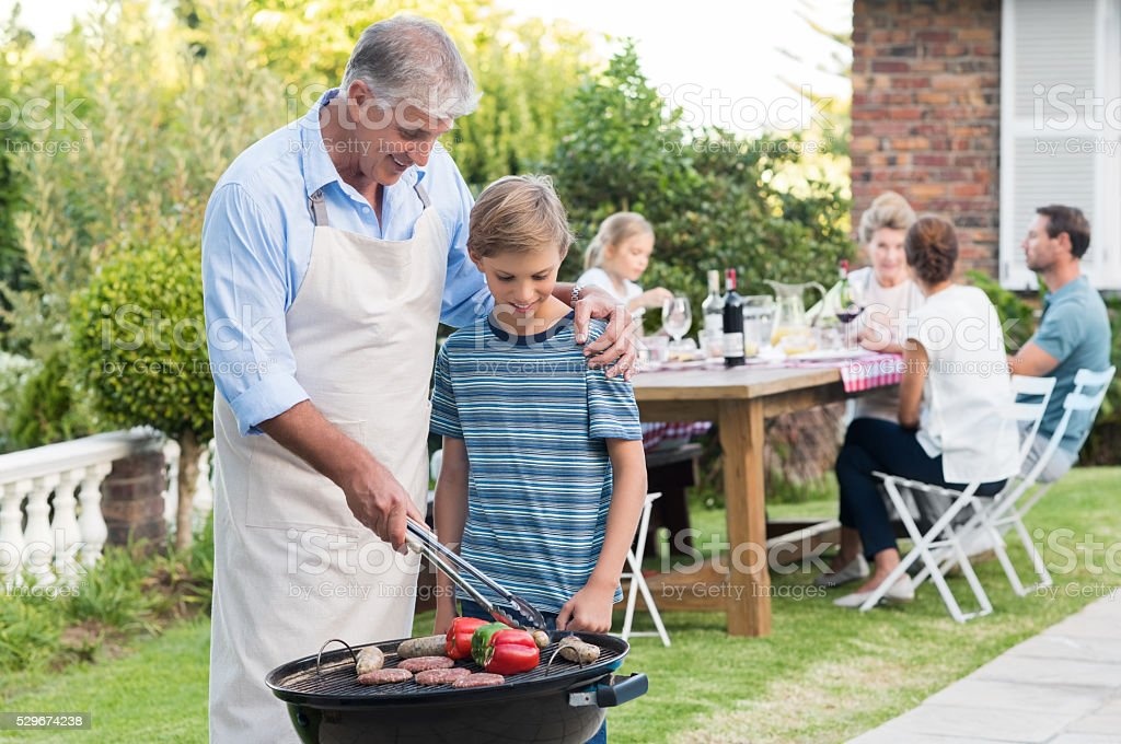 Grandfather cooking with grandson stock photo