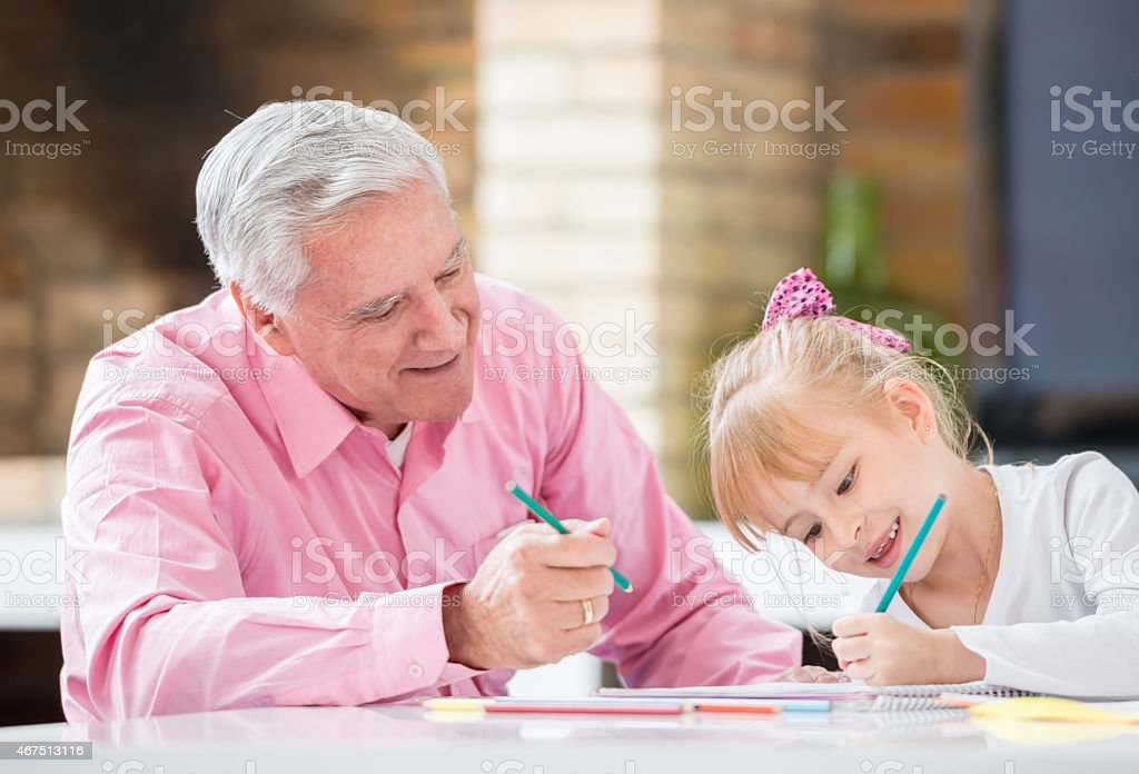 Grandfather drawing with his granddaughter stock photo