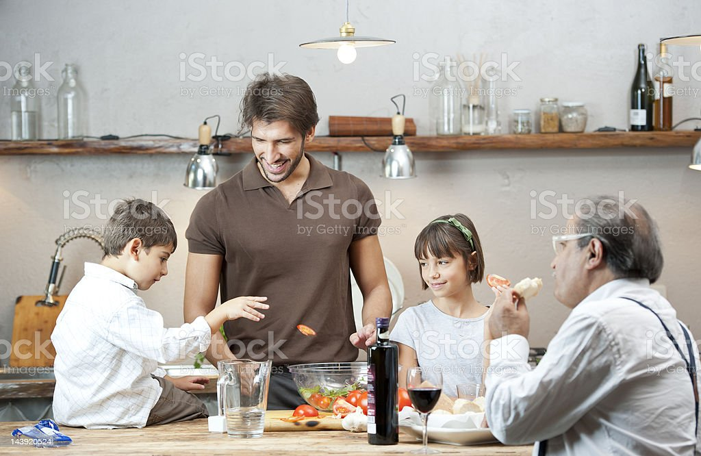 Grandfather, father and children cooking together royalty-free stock photo