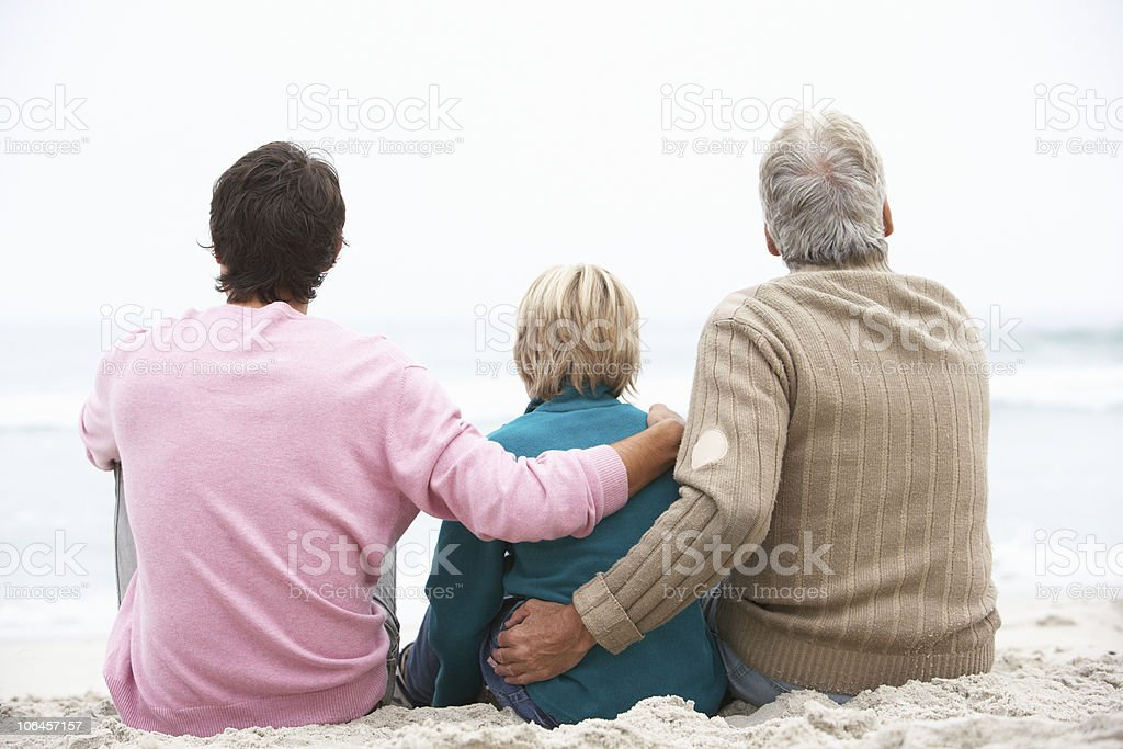 Grandfather, Father And Grandson Sitting On Winter Beach royalty-free stock photo