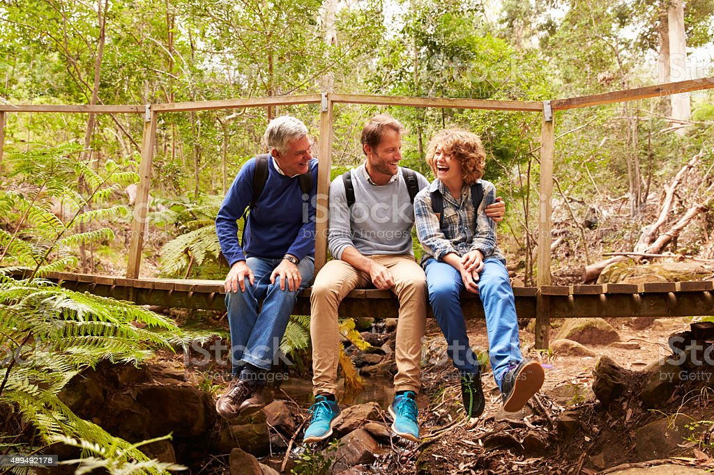 Grandfather, father and son sitting on a bridge in forest stock photo