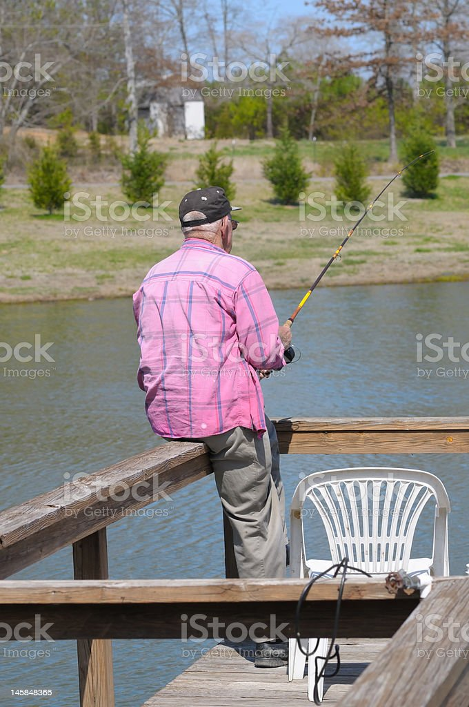 Grandfather Fishing Off a Dock royalty-free stock photo