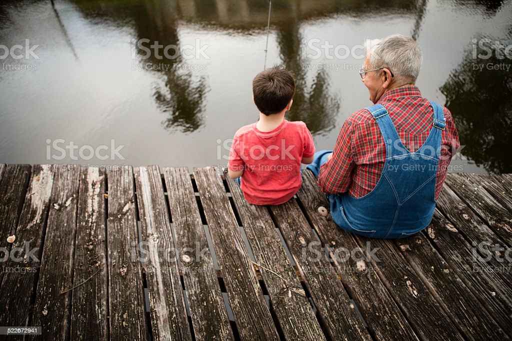 Grandfather Fishing with Great Grandson on Wooden Dock stock photo