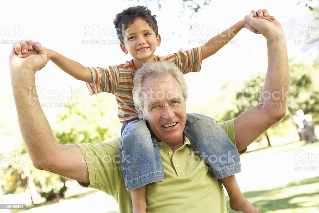 A grandfather giving his grandson a ride on his shoulders royalty-free stock photo