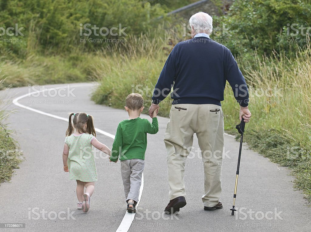Grandfather going on a walk with his grandchildren royalty-free stock photo