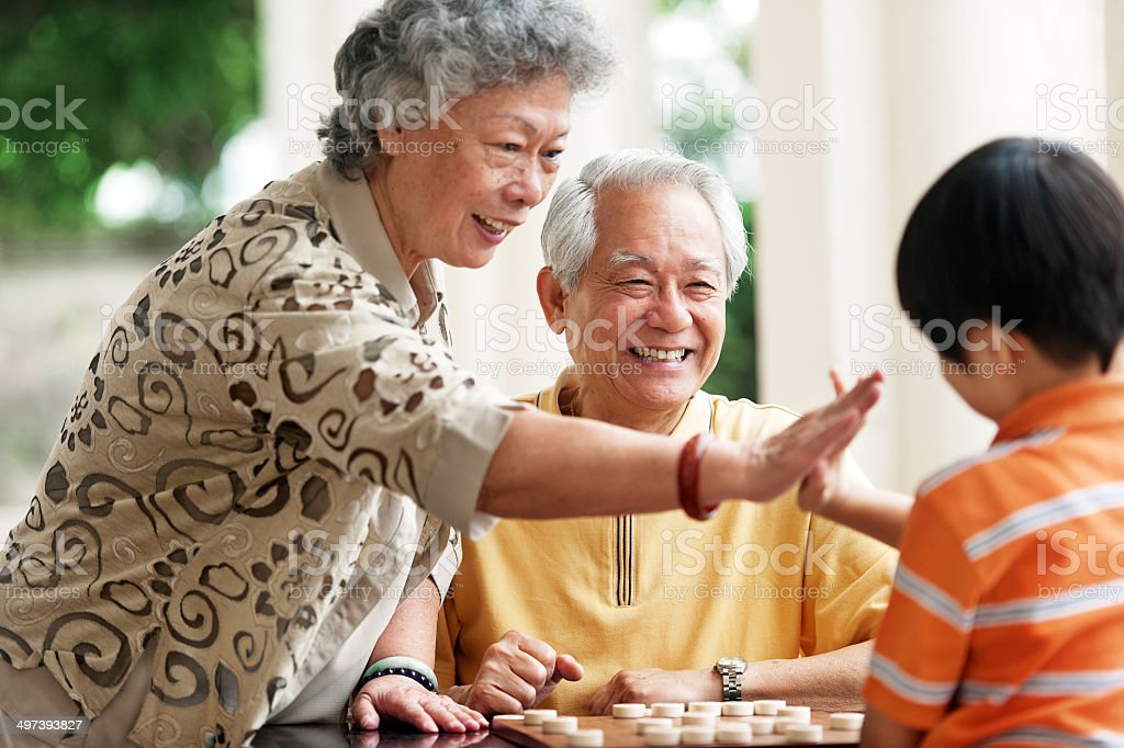 Grandfather, grandmother and grandson playing Xiangqi (chinese chess) stock photo
