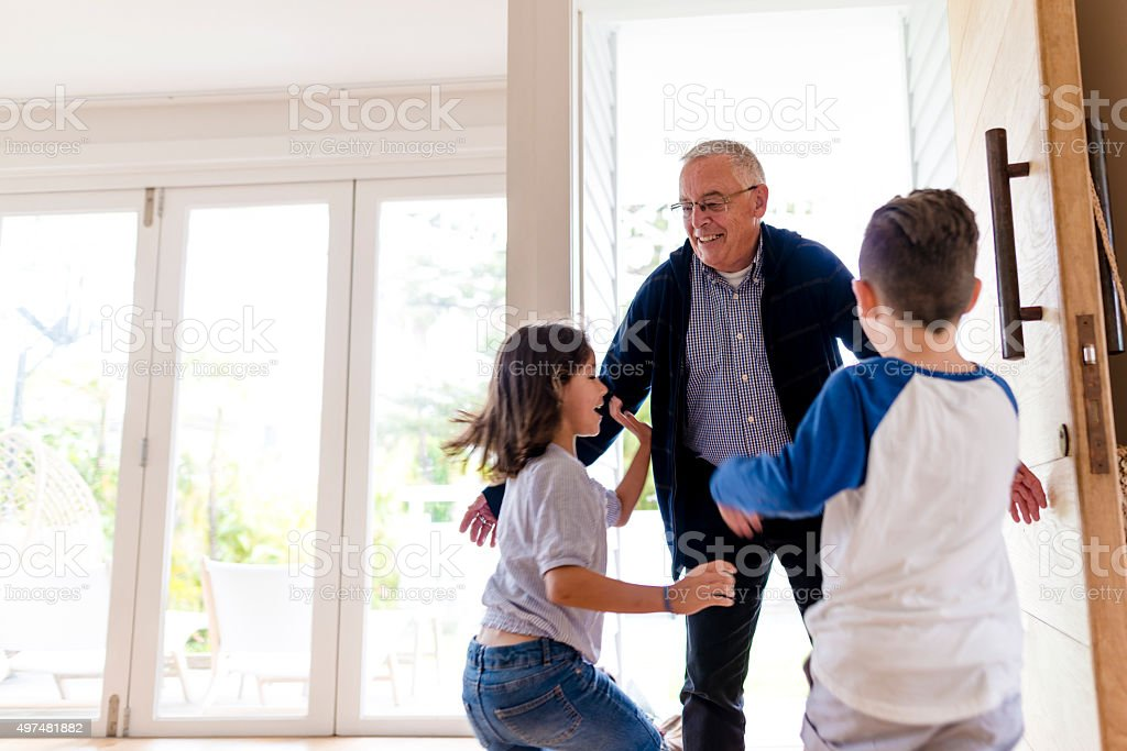Grandfather greeting his children stock photo