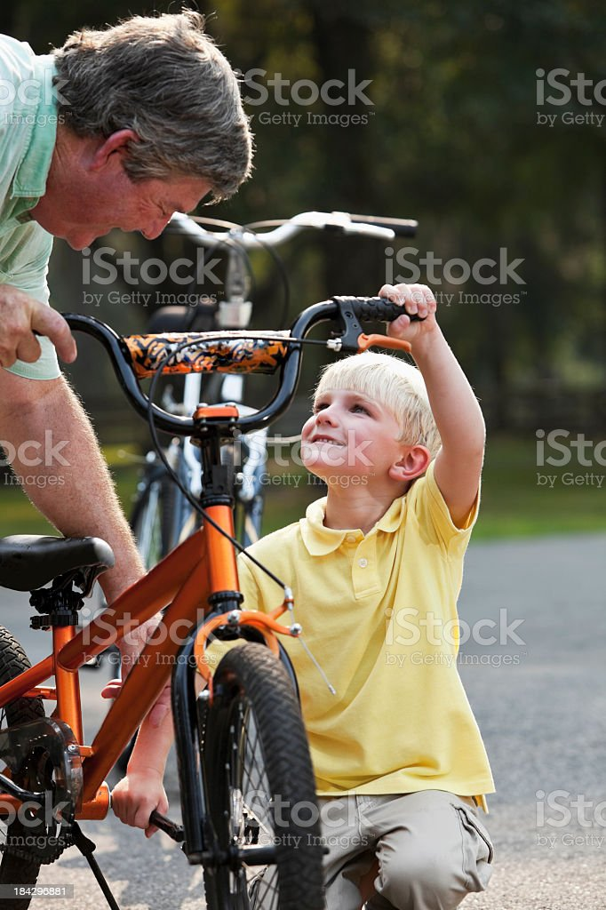 Grandfather helping little boy with bicycle stock photo