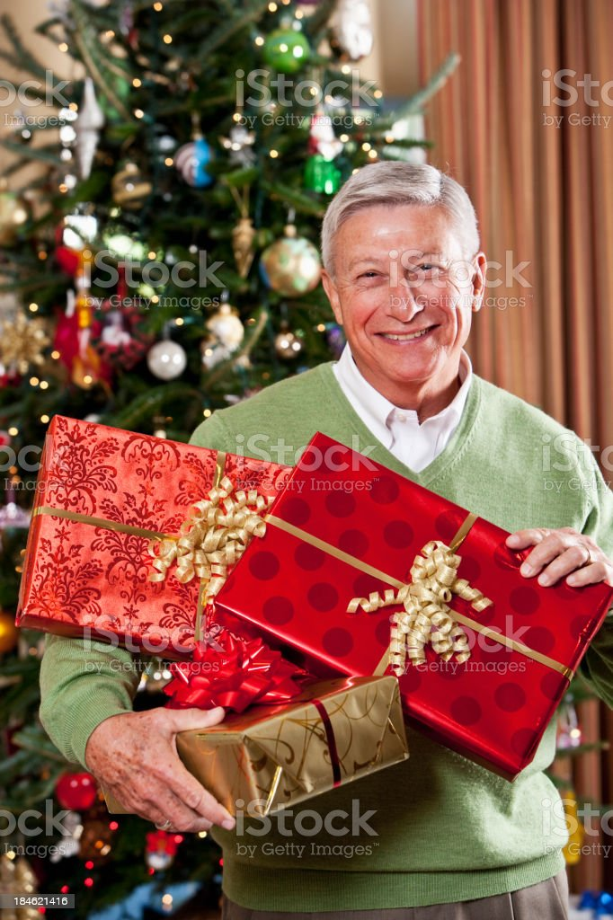 Grandfather holding gifts by Christmas tree stock photo