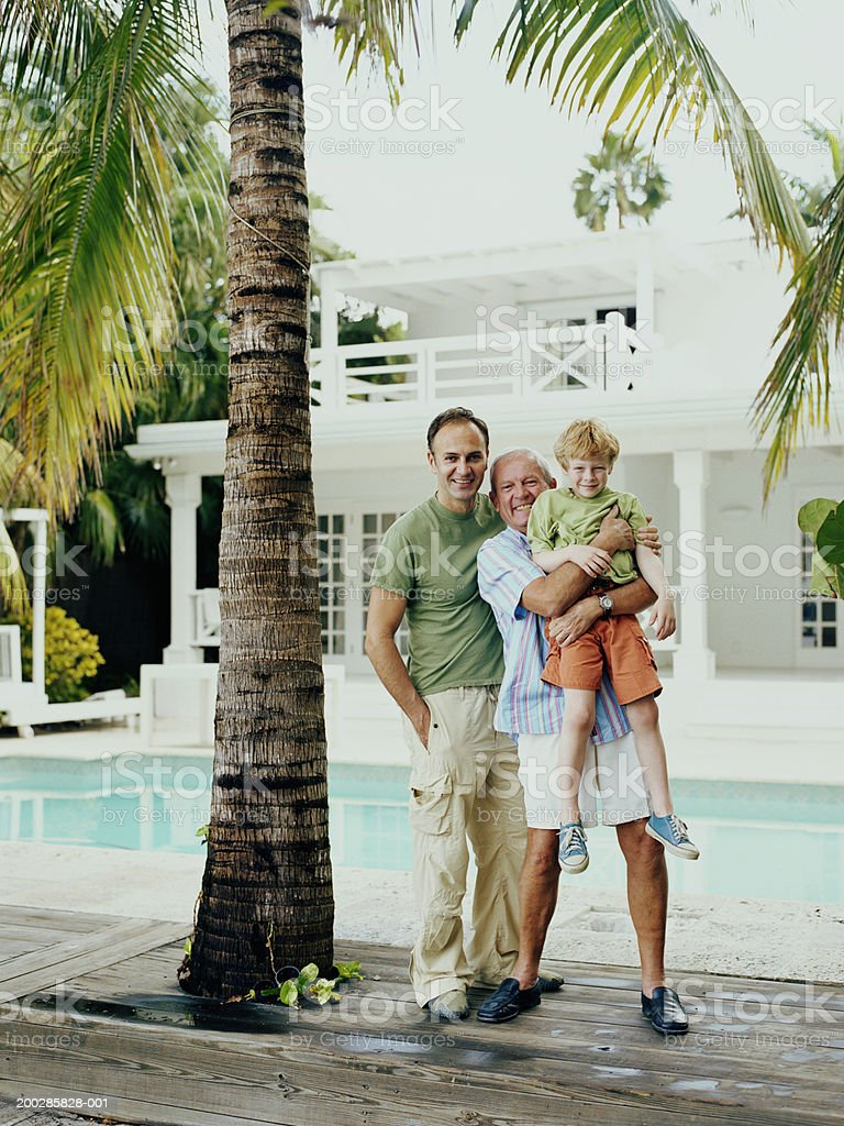 Grandfather holding grandson (5-7) standing with son by pool, smiling royalty-free stock photo