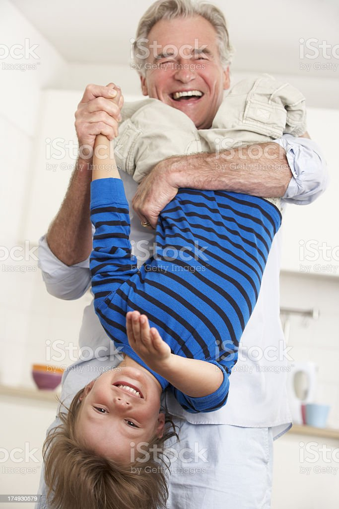 Grandfather Holding Grandson Upside Down At Home stock photo