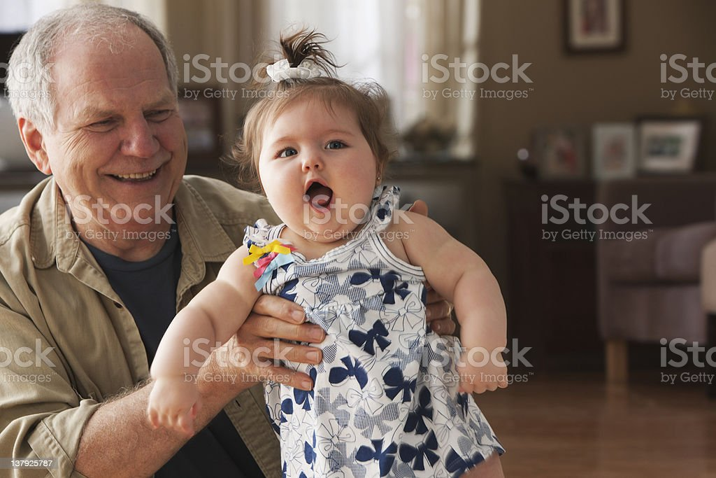 Grandfather holding happy granddaughter royalty-free stock photo