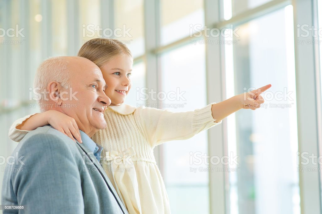 Grandfather holding his granddaughter and communicating stock photo