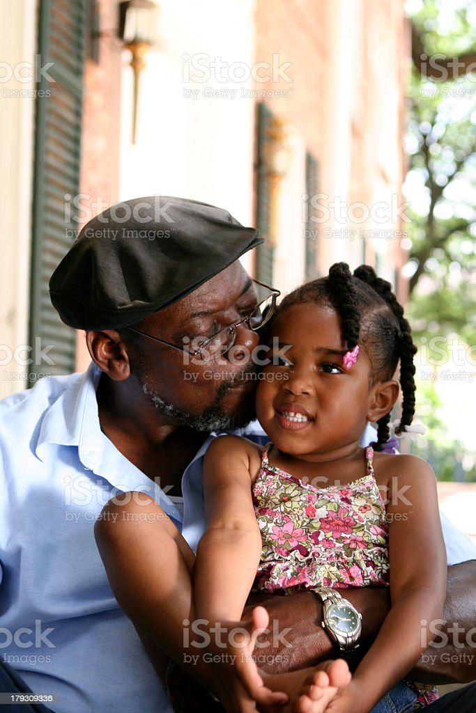 Grandfather hugging and kissing his granddaughter stock photo