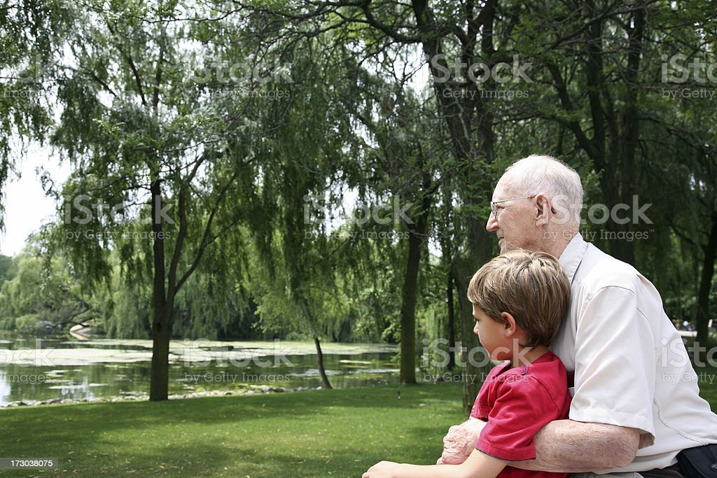 Grandfather hugs his Grandson at the park royalty-free stock photo
