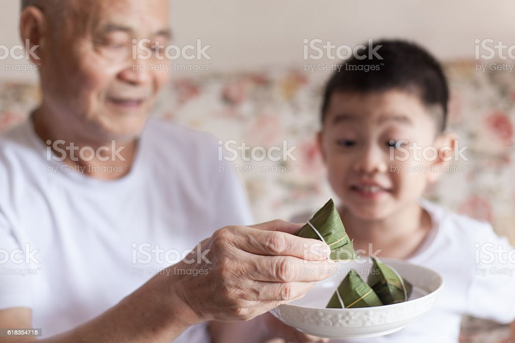 Grandfather introducing grandson to zongzi stock photo