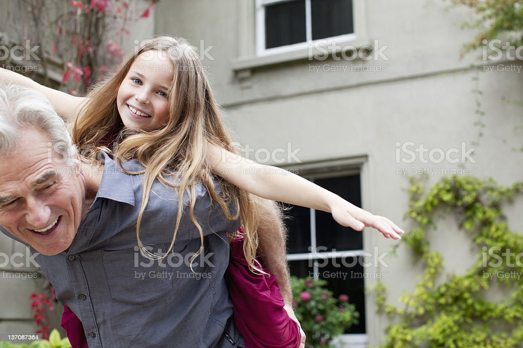 Grandfather piggybacking granddaughter stock photo