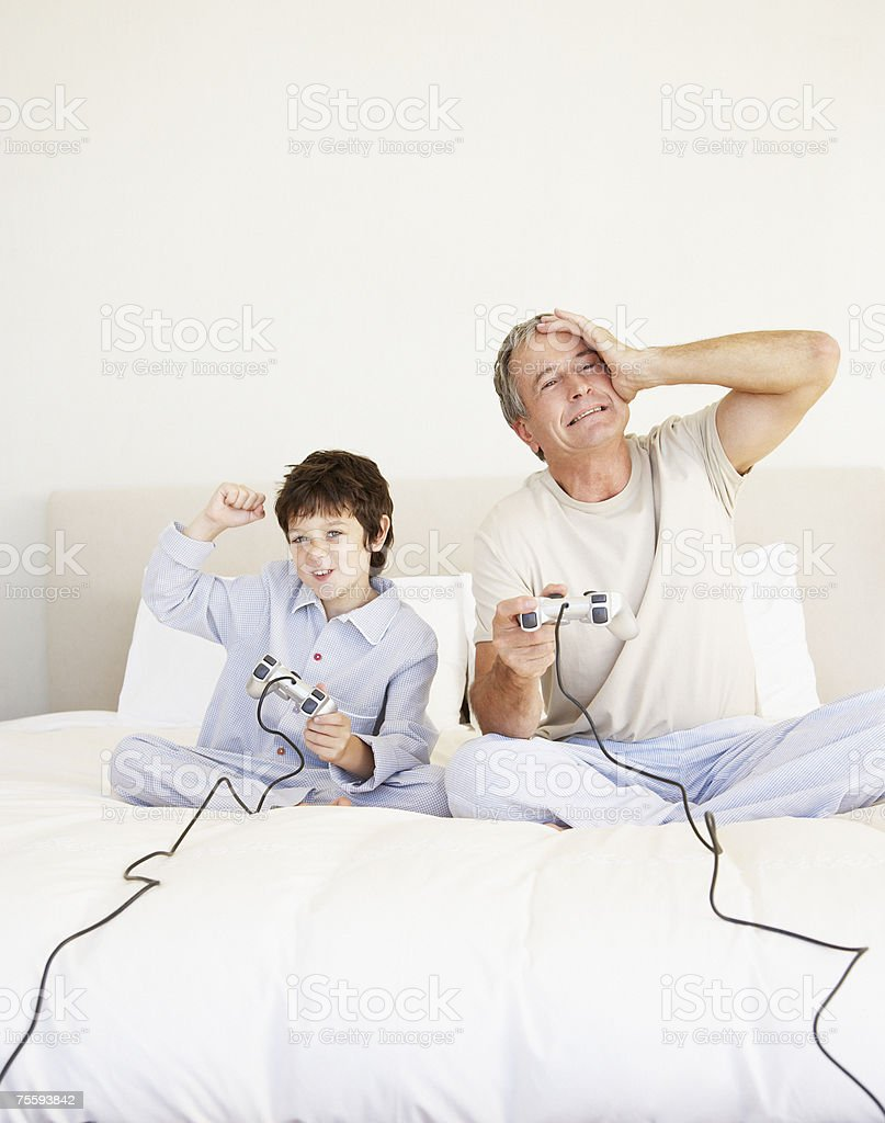A grandfather playing video games with his grandson in bed royalty-free stock photo