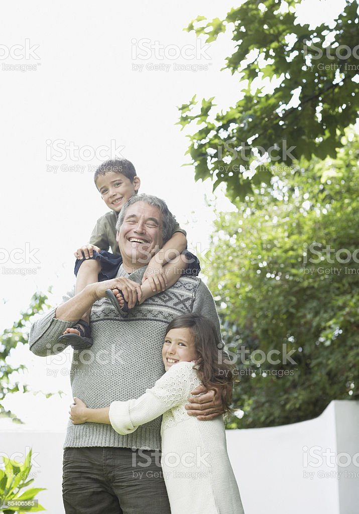 Grandfather playing with grandchildren in backyard royalty-free stock photo