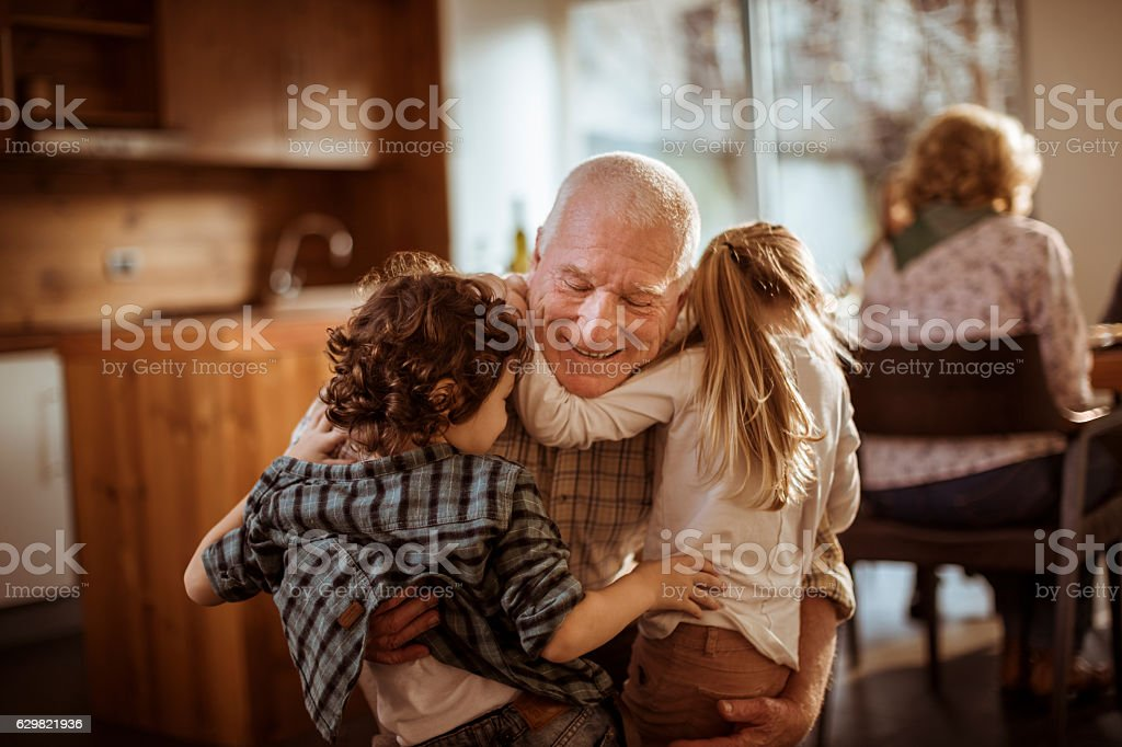 Grandfather playing with his grandkids stock photo