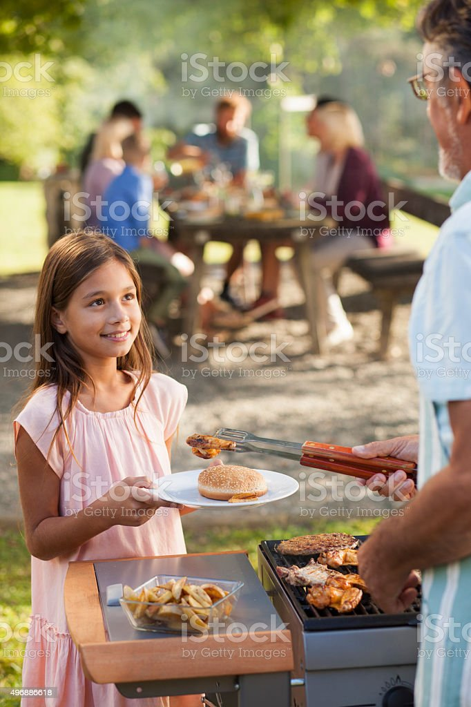 Grandfather preparing food for his family stock photo