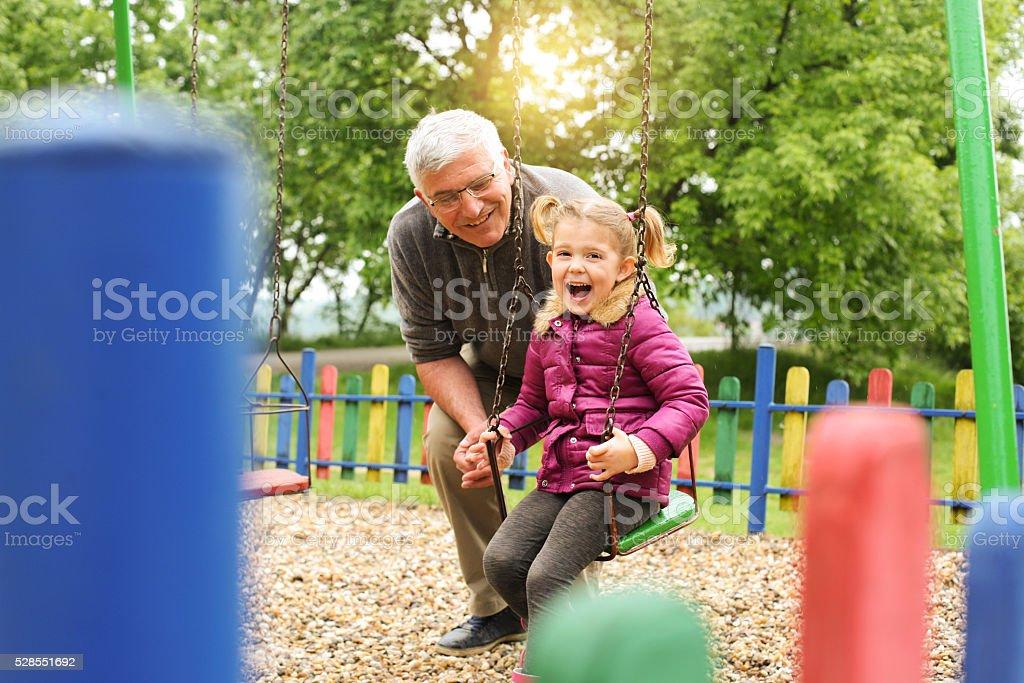 Grandfather pushing granddaughter on swing. stock photo