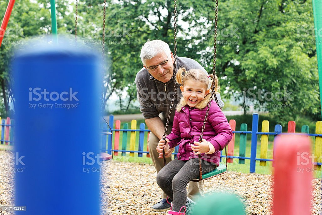 Grandfather pushing granddaughter on swing. stock photo