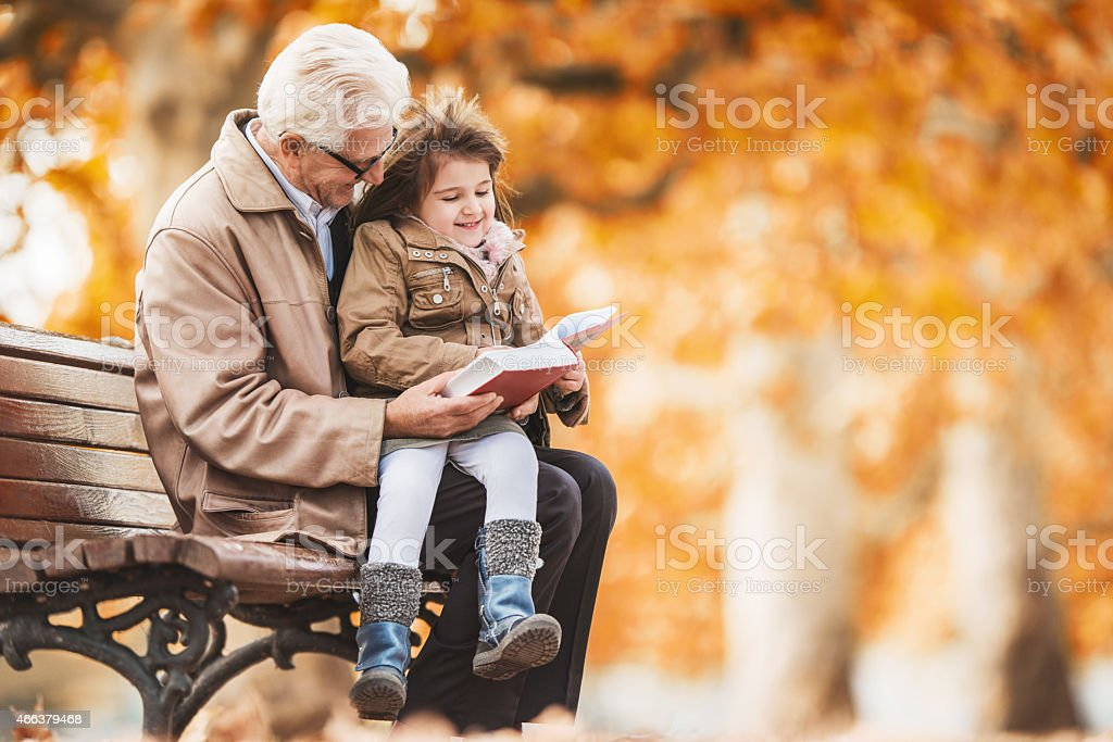 Grandfather reading a book to little girl in the park. stock photo