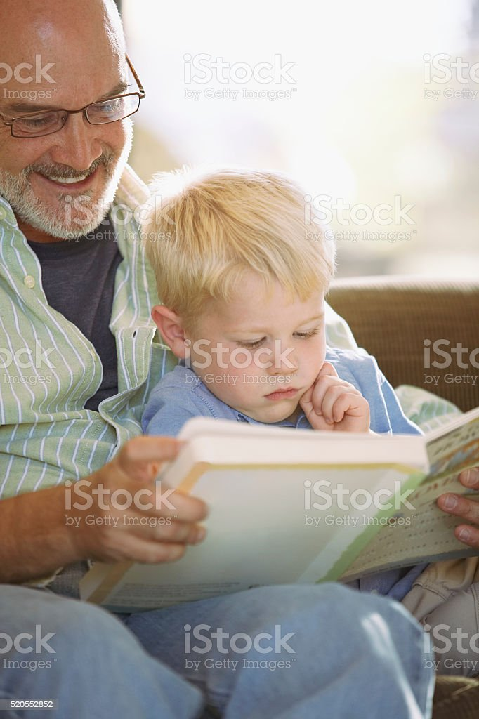 Grandfather reading to his grandson stock photo