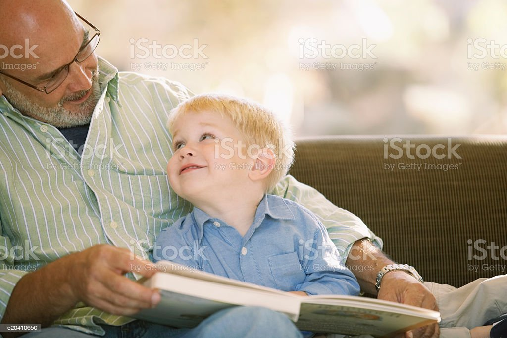 Grandfather reading with his grandson stock photo