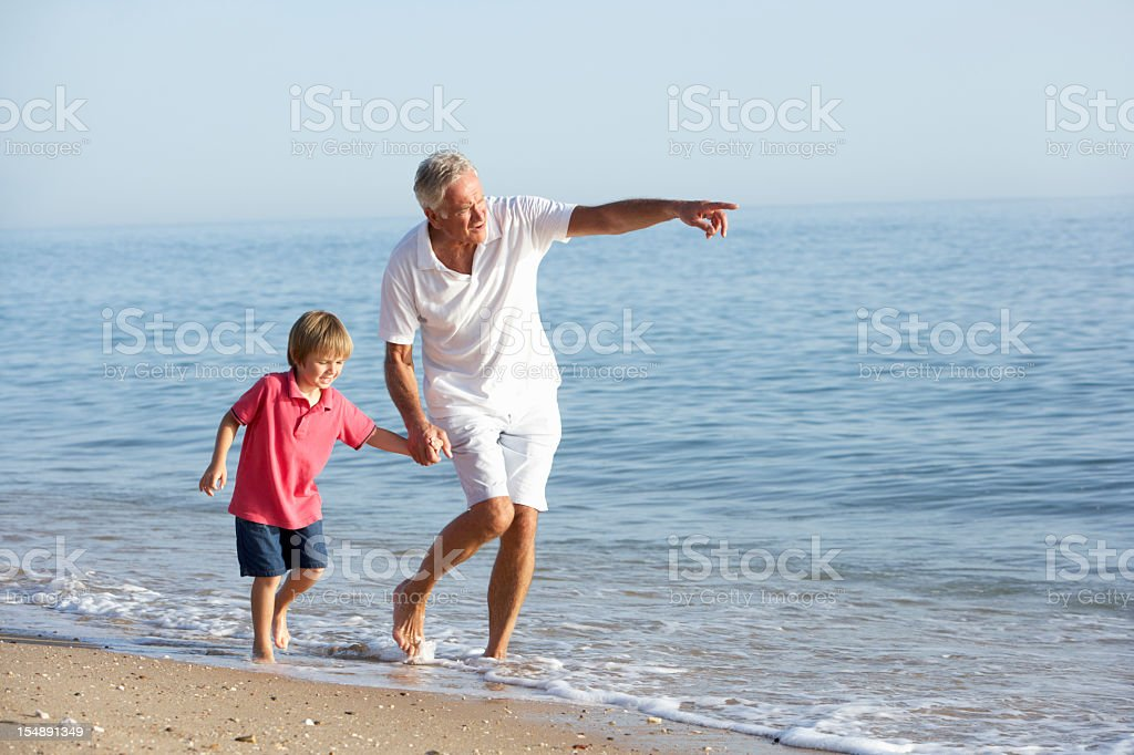 A grandfather shows his grandson around the beach royalty-free stock photo