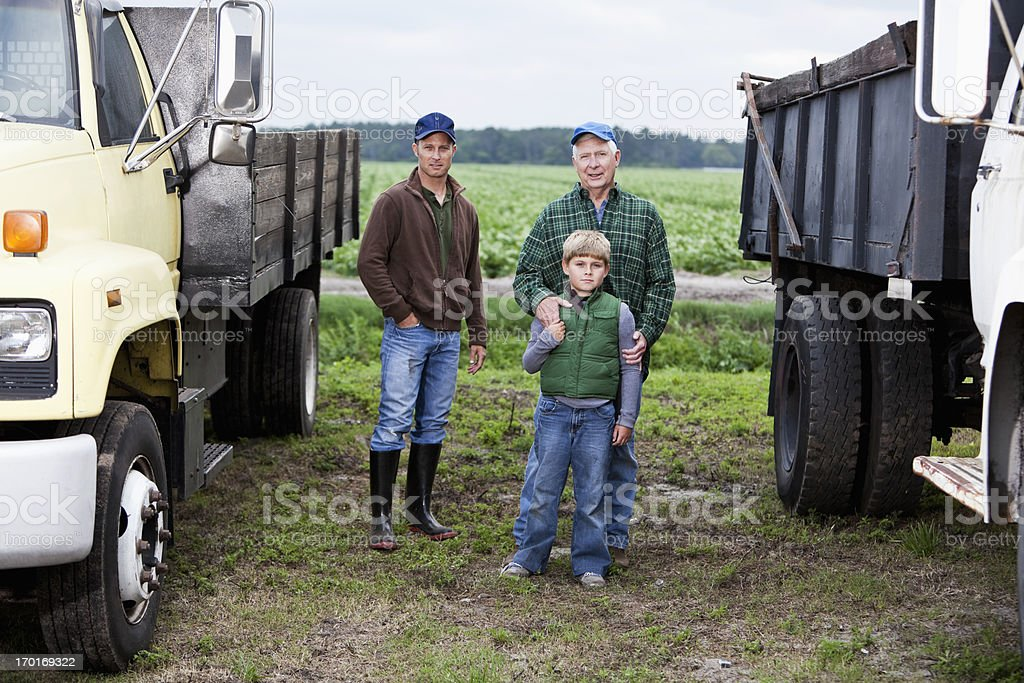 Grandfather, son and grandson on family farm with trucks stock photo