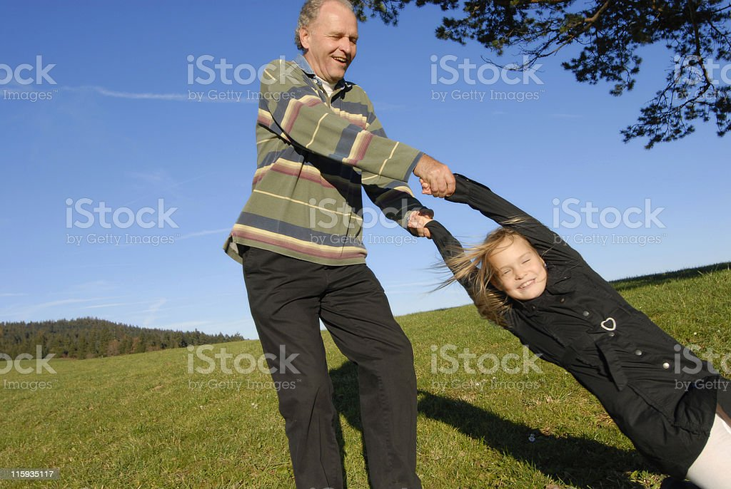 Grandfather swinging granddaughter by arms outside on hill royalty-free stock photo