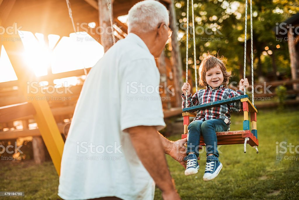 Grandfather swinging his happy grandson at sunset. stock photo